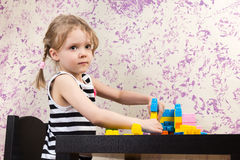Little girl builds bricks at table Royalty Free Stock Image