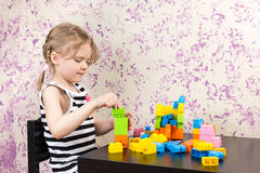 Little girl builds bricks at table Royalty Free Stock Photo