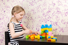 Little girl builds bricks at table Stock Photos