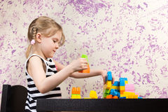 Little girl builds bricks at table Stock Image