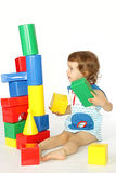 A little girl builds a house. Stock Photo