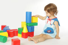 A little girl builds a house. Royalty Free Stock Image