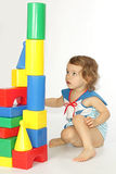A little girl builds a house. A little girl builds a house from the coloured details Stock Photos