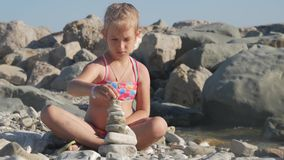 Little girl builds a pebble tower sitting on the beach by the sea. The concept of a child`s dream. Little girl builds a pebble tower sitting on the beach by the stock video footage