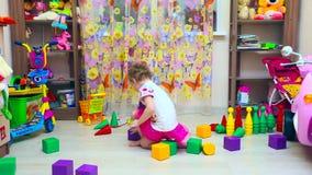 Little girl builds pyramid of blocks stock video