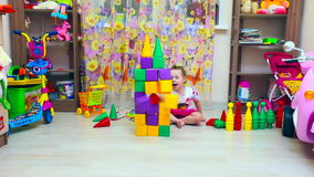 Little girl builds pyramid of blocks stock footage