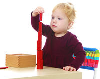 Little girl builds a pyramid sitting at the table Royalty Free Stock Images