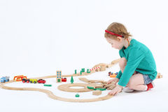 Little girl builds railway from wooden parts  on floor Royalty Free Stock Photography