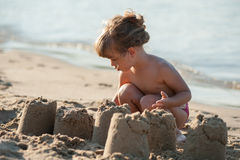 Little girl builds a sand castle. On the beach Royalty Free Stock Image