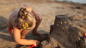 Little girl builds a sand castle stock video