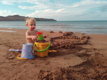 little girl builds a sand castle Stock Image