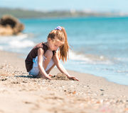 Little girl  builds a tower of sand Stock Photography