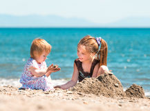 Little girl  builds a tower of sand Royalty Free Stock Images