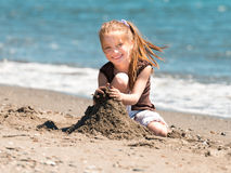 Little girl  builds a tower of sand Royalty Free Stock Image
