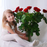 Little girl with a bunch of red roses Stock Images