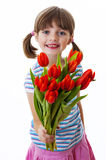 Little girl with bunch of red tulips Stock Images