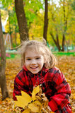 Little girl with a bunch of yellow leaves Stock Photos