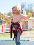 Little girl on bungee trampoline. Royalty Free Stock Images