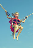 Little girl on bungee trampoline. Royalty Free Stock Image