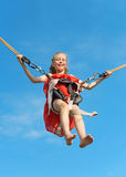 Little girl on bungee trampoline. Stock Images