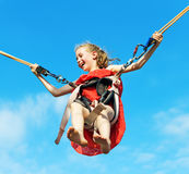 Little girl on bungee trampoline. Stock Photos