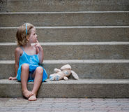 Little Girl with Bunny on Concrete Steps Stock Images