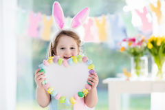 Little girl in bunny ears on Easter egg hunt. Happy little girl in bunny ears holding a heart board with colorful Easter eggs. Kids celebrate Easter. Children Stock Photography