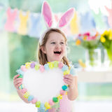 Little girl in bunny ears on Easter egg hunt. Happy little girl in bunny ears holding a heart board with colorful Easter eggs. Kids celebrate Easter. Children Royalty Free Stock Images