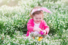 Little girl with bunny ears on Easter egg hunt Royalty Free Stock Image