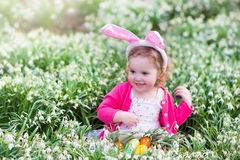 Little girl with bunny ears on Easter egg hunt Stock Images