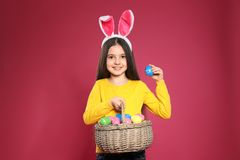 Little girl in bunny ears headband holding basket with Easter eggs royalty free stock photography