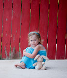 Little Girl with Bunny next to Red Fence Stock Photos