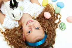 Little girl with a bunny rabbit has a easter at white carpe Royalty Free Stock Photography