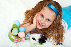 Little girl with a bunny rabbit has a easter at white carpe Stock Photos