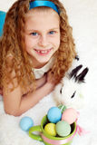 Little girl with a bunny rabbit has a easter at white carpe Stock Images
