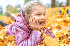 Little girl buried in autumn leaves yellow Stock Photography