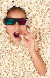 Little girl buried in popcorn. Wearing 3d glasses Stock Photo