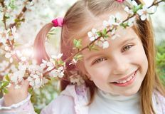 Little girl with bush blossoming Stock Image