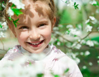 Little girl with bush blossoming tree Stock Photography