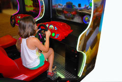Little girl is busy with game machine stock image