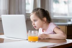 Little girl busy playing computer in kitchen at home. Child sitting at table watching cartoons on notebook. Addiction to computers, gadgets, bad habit. New royalty free stock images
