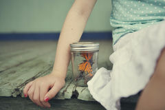 Little girl with butterfly. A little girl sitting on a porch with a butterfly in a jar royalty free stock photo