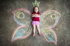 Little girl Butterfly, CAPRICE. Drawing with chalk on the pavement royalty free stock photo