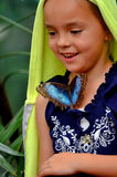 Little girl with a butterfly on her shirt. Happy little girl smiling with yellow towel over her head and a butterfly on her blue flowered shirt stock image