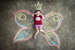 Little girl Butterfly, HIDE AND SEEK. Drawing with chalk on the pavement Stock Photo