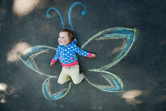Little Girl Butterfly. Little girl smiling Butterfly, drawing with chalk on the pavement Stock Photos