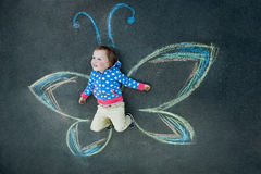 Little girl Butterfly smiling. Drawing with chalk on the pavement Royalty Free Stock Photography