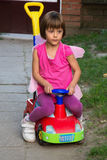 Little girl with butterfly wings having fun in car toy royalty free stock photography