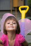 Little girl with butterfly wings having fun in car toy royalty free stock photos