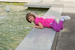 Little girl with butterfly wings having fun in a fountain stock photo